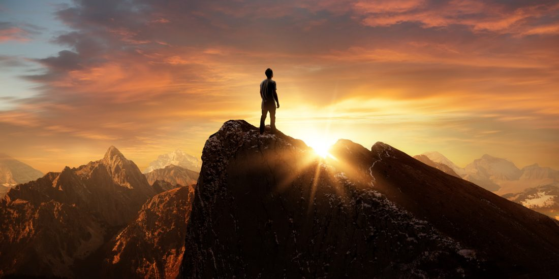 Man standing on mountain looking at sunrise